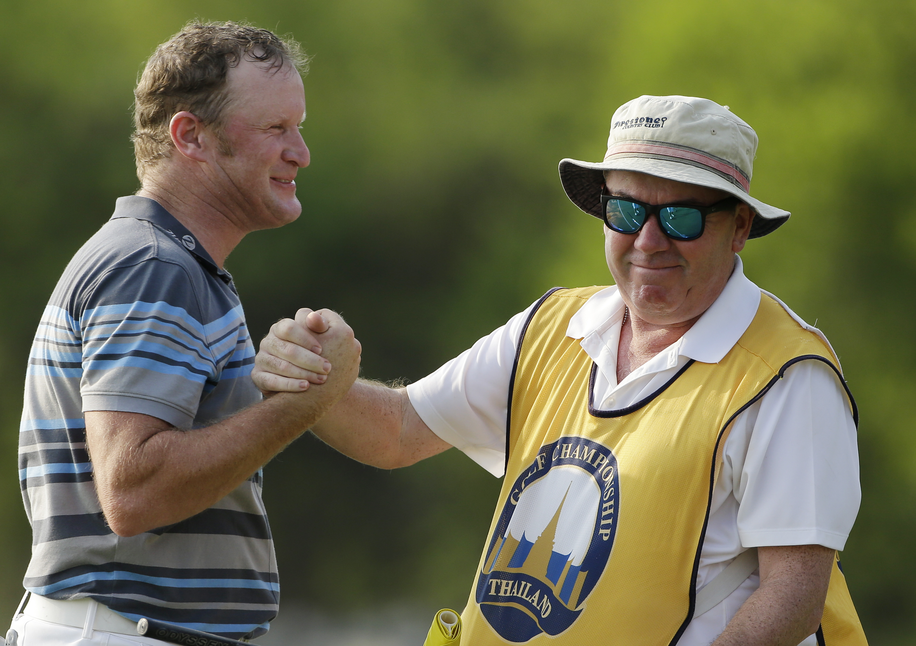 Jamie Donaldson is congratulated by his caddie Michael Donnegy, right, after winning the Thailand Golf Championship at the Amata Spring Country Club, Chonburi, Thailand, on Sunday, Dec. 13, 2015.