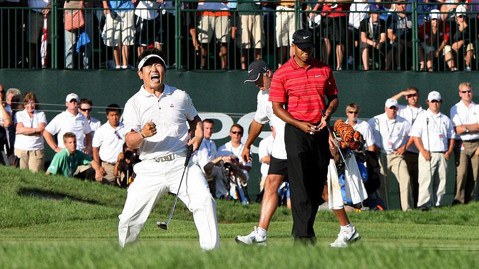 Y.E. Yang of South Korea celebrates a birdie putt on the 18th green alongside Tiger Woods during the final round of the 91st PGA Championship at Hazeltine National Golf Club on August 16, 2009 in Chaska, Minnesota.