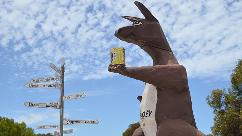 "The ""Rooey II"" big roo sculpture at the roadhouse at Border Village, South Australia. Behind ""Rooey II"" is the 160 m long ""Hole 6: Border Kangaroo"" of the Nullarbor Links golf course."