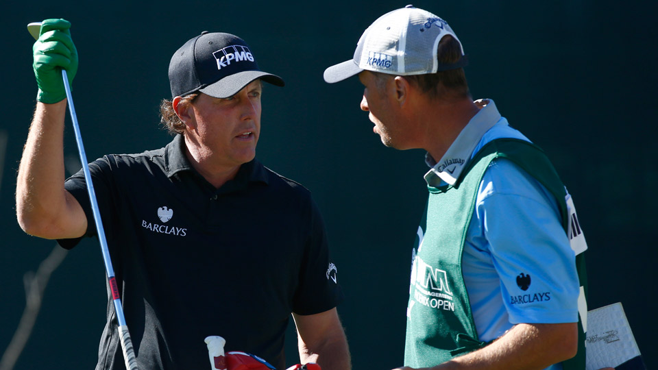 """Phil Mickelson strategizes with his caddie Jim """"Bones"""" Mackay during the 2016 Waste Management Phoenix Open"""