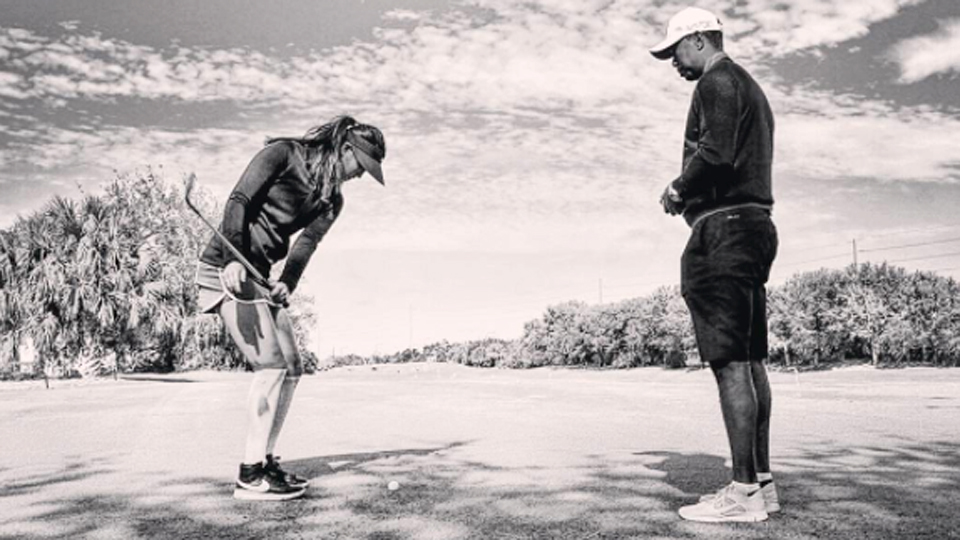 Michelle Wie chips as Tiger Woods watches.