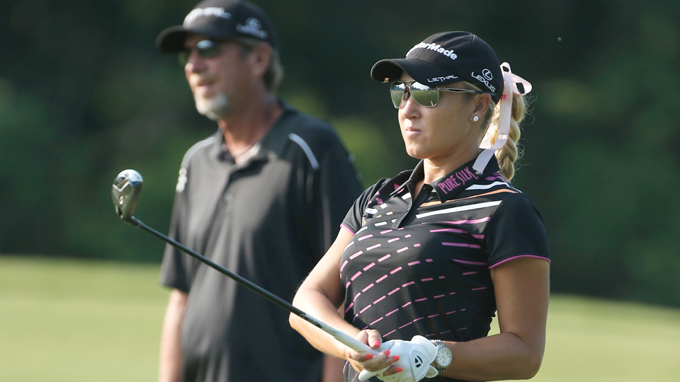 Natalie Gulbis hits a shot as her caddie Greg Sheridan looks on during a practice round prior to the start of the 2013 U.S. Women's Open.