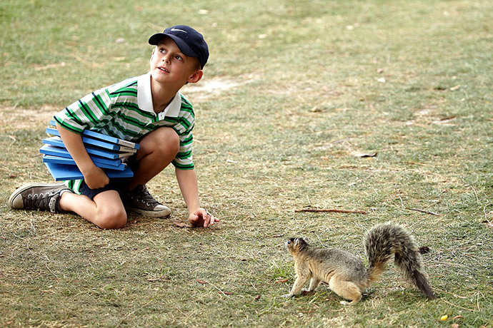 A young fan interacts with a fox squirrel during the final round of the Valspar Championship at Innisbrook Resort Copperhead Course.