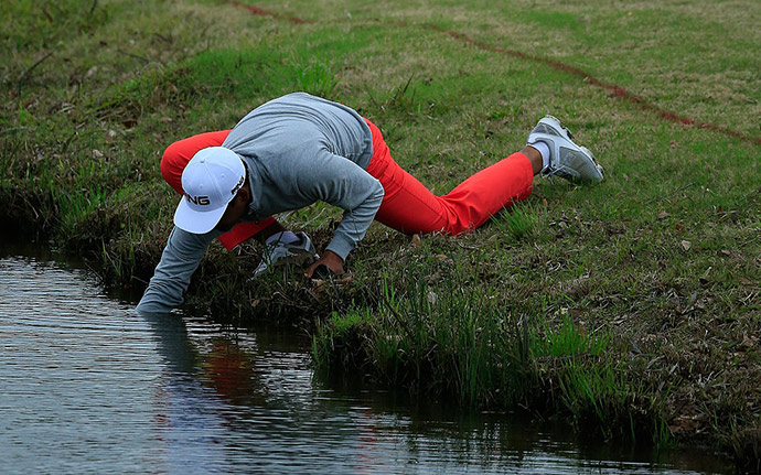 Sebastian Munoz of Colombia retrieves his ball from the water hazard on the 18th hole during the third round of the Chitimacha Louisiana Open