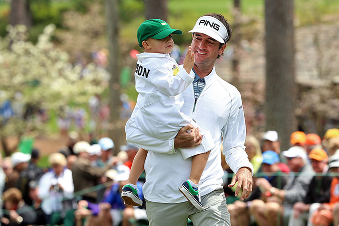 Bubba Watson of the United States carries his son Caleb during the Par 3 Contest.