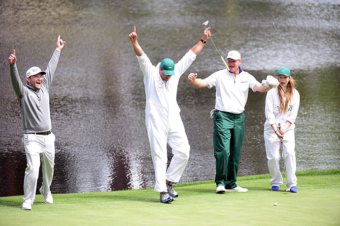 Caddie Zacharia Rasego celebrates putting with Branden Grace of South Africa and Ernie Els of South Africa during the Par 3 Contest.