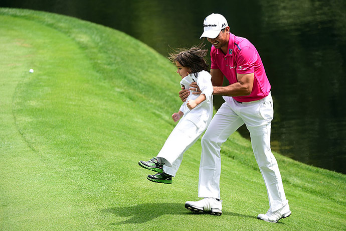 Jason Day of Australia and his son Dash walk during the Par 3 Contest.