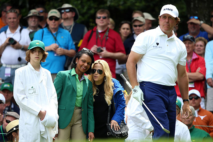 Phil Mickelson of the United States is watched by wife Amy, son Evan and Former United States Secretary of State Condoleezza Rice during the Par 3 Contest.