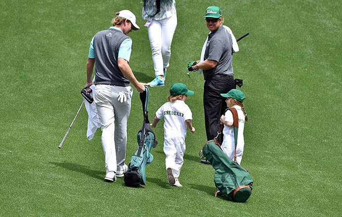 US golfer Brandt Snedeker (L) walks with his son Austin during the Par 3 contest.