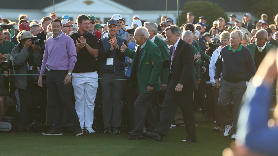 Arnold Palmer walks to the first tee to take part in the ceremonial first tee shots at the Masters on Thursday at Augusta National Golf Club. Amateur Bryson DeChambeau, in white pants, claps in the background.