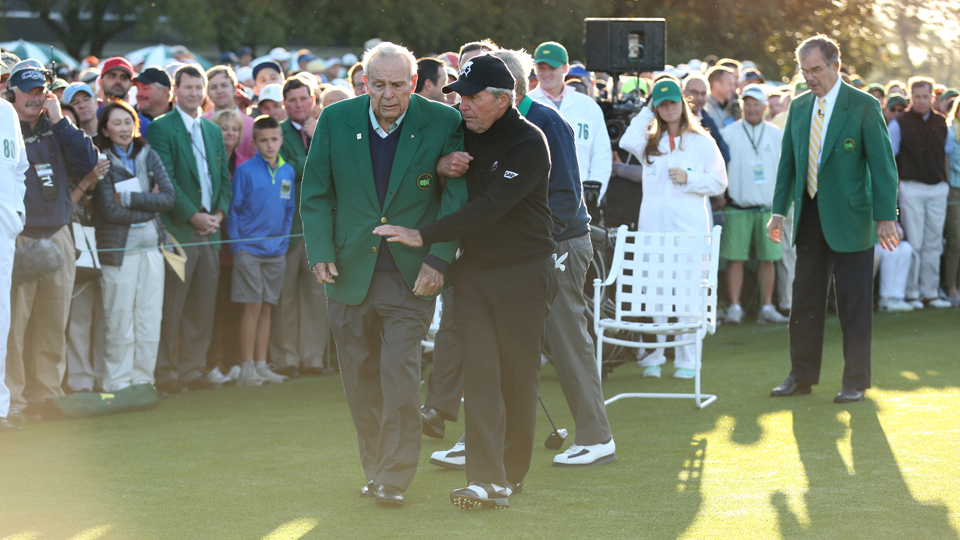 Gary Player helps Arnold Palmer walk to a spot on the first tee for a photo after the ceremonial first tee shots on Thursday.