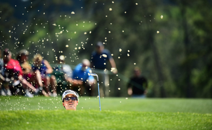 Kevin Na hits out of a bunker during the first round.