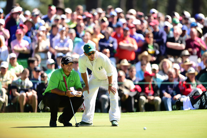 Patrick Reed and his caddie read a putt on the sixth green.