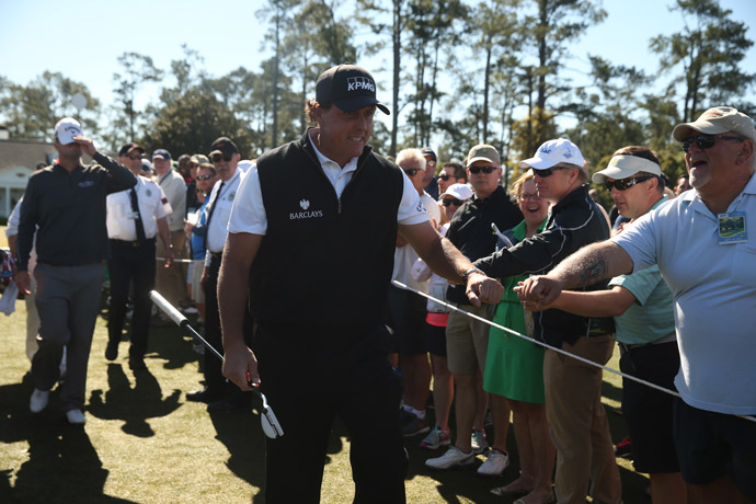 Phil Mickelson greets patrons as he walks to the first tee to start round 1.