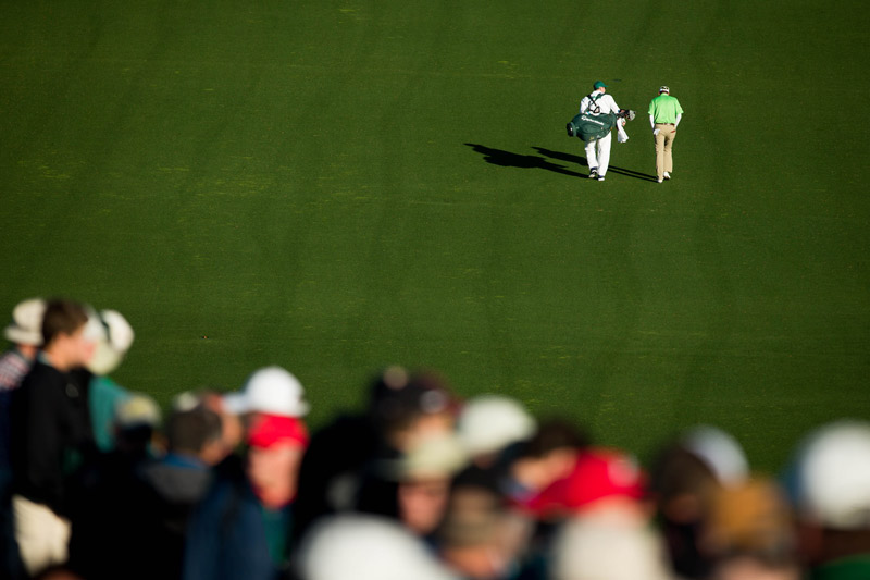 After hitting the first tee shot of the 2016 Masters, Jim Herman and his caddie walk down the first fairway