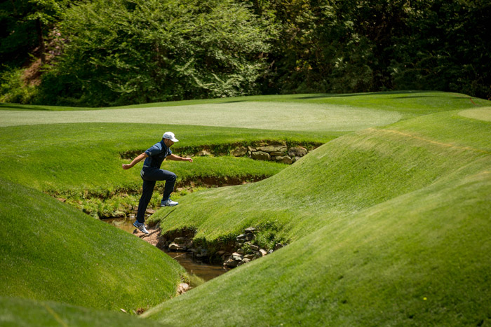 Sergio Garcia leaps through Rae's Creek during the second round.