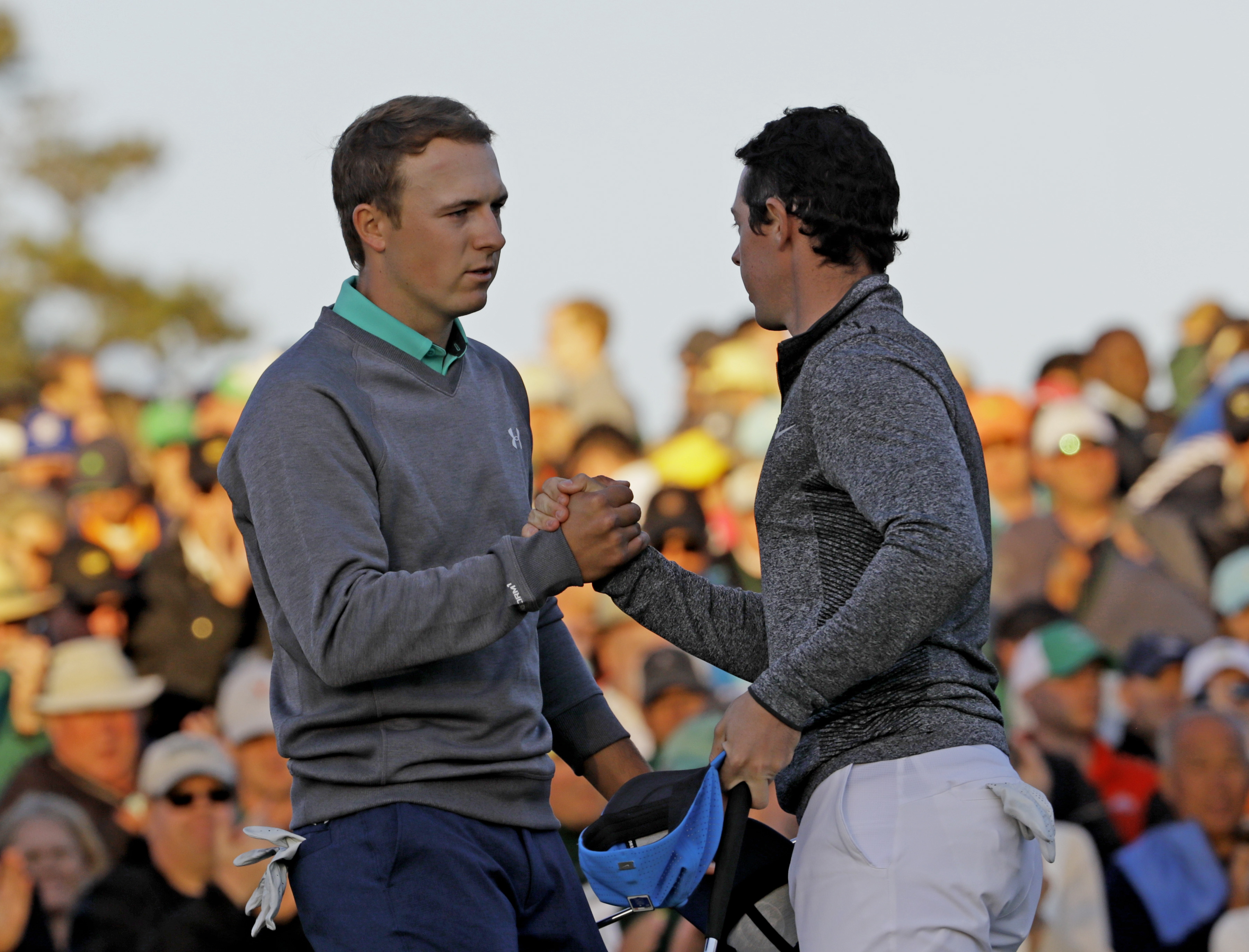 Jordan Spieth, left, shakes hands with Rory McIlroy, of Northern Ireland, on the 18th green during the third round of the Masters golf tournament Saturday, April 9, 2016.