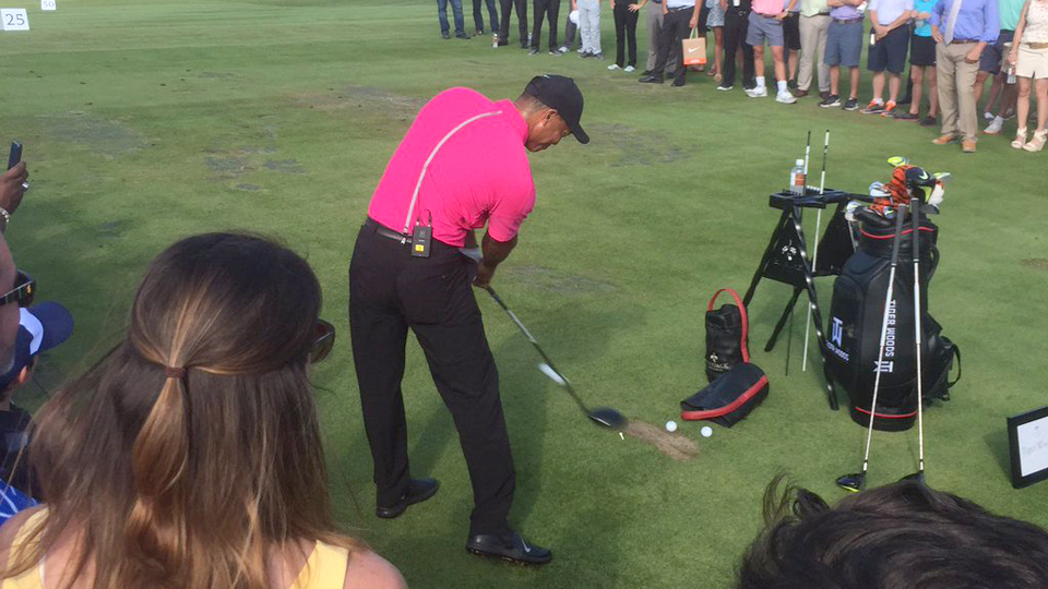 Tiger Woods hits a tee shot with fans watching at the opening of Bluejack National on Monday.