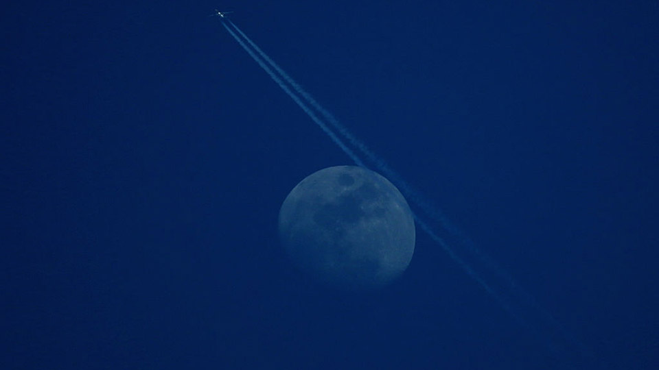 A plane passes across the moon during the third round of the Omega Dubai Desert Classic on the Majlis Course at the Emirates Golf Club.