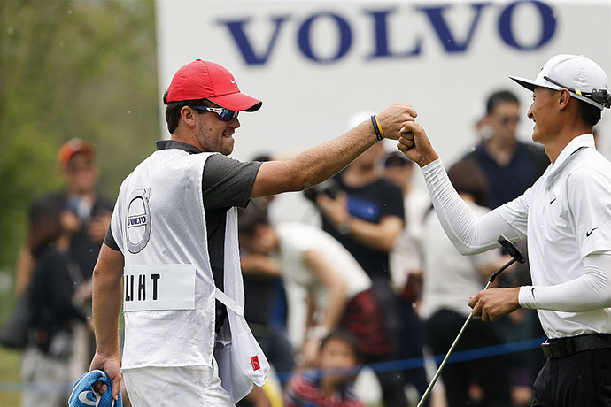 Li Haotong of China celebrates after he plays a shot with his caddy during the final round of the Volvo China open at Topwin Golf and Country Club