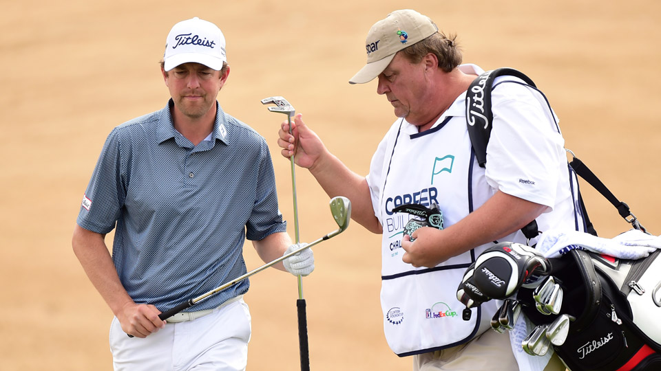 Caddie Eric Bajas, aka 'Big E,' hands Bryce Molder his putter during the CareerBuilder Challenge in January. Bajas, just like all the pros, is chasing his own number on the course.