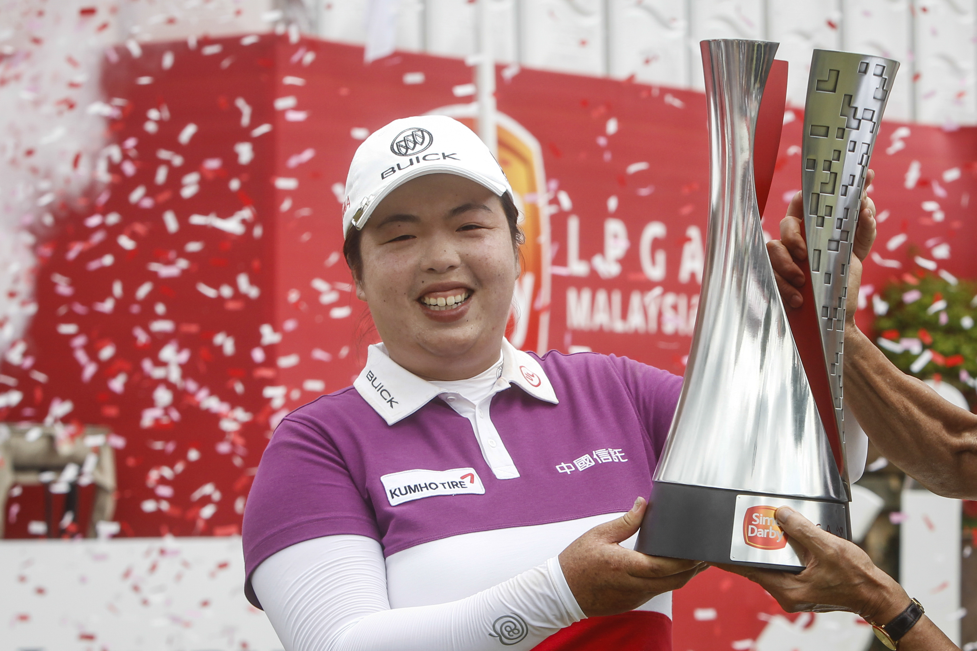 Shanshan Feng of China holds up her trophy after winning the LPGA golf tournament at Tournament Players Club (TPC) in Kuala Lumpur, Malaysia, Sunday, Oct. 30, 2016.