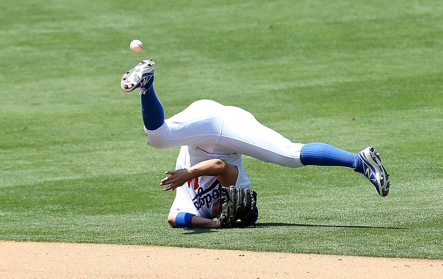 Shortstop Kike Hernandez of the Los Angeles Dodgers flips the ball to second base in an unsuccessful attempt to get a runner out in a game against the New York Mets.