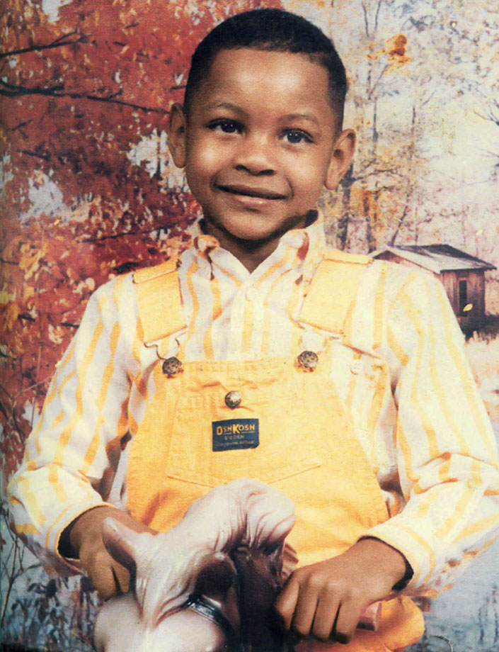 A very young Carmelo poses on a toy horse. How cute.