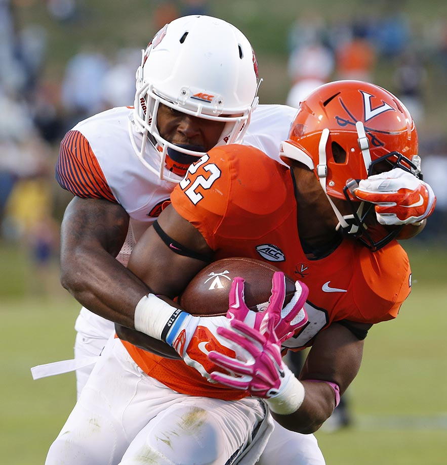 Corey Winfield of Syracuse grabs the face mask of Virginia running back Daniel Hamm and was called for a penalty. Virginia won 44-38 in triple overtime.