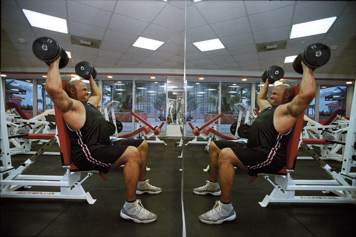 Former NBA star and TNT announcer Charles Barkley lifting weights at hotel gym in Miami, Florida in 2002.