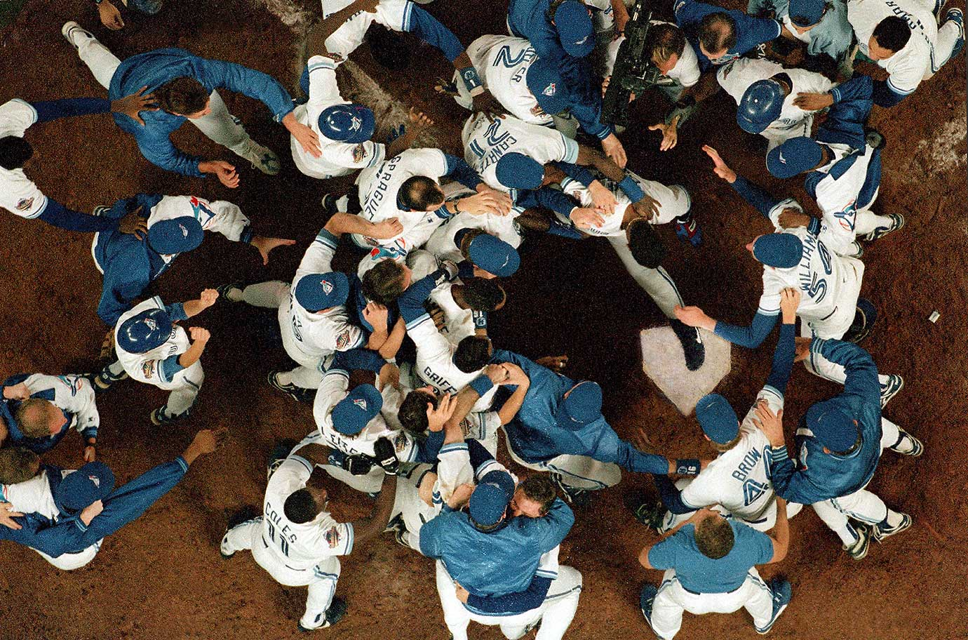 Toronto Blue Jays players greeting Joe Carter at home plate after his World Series-winning home run in 1993 against the Philadelphia Phillies.