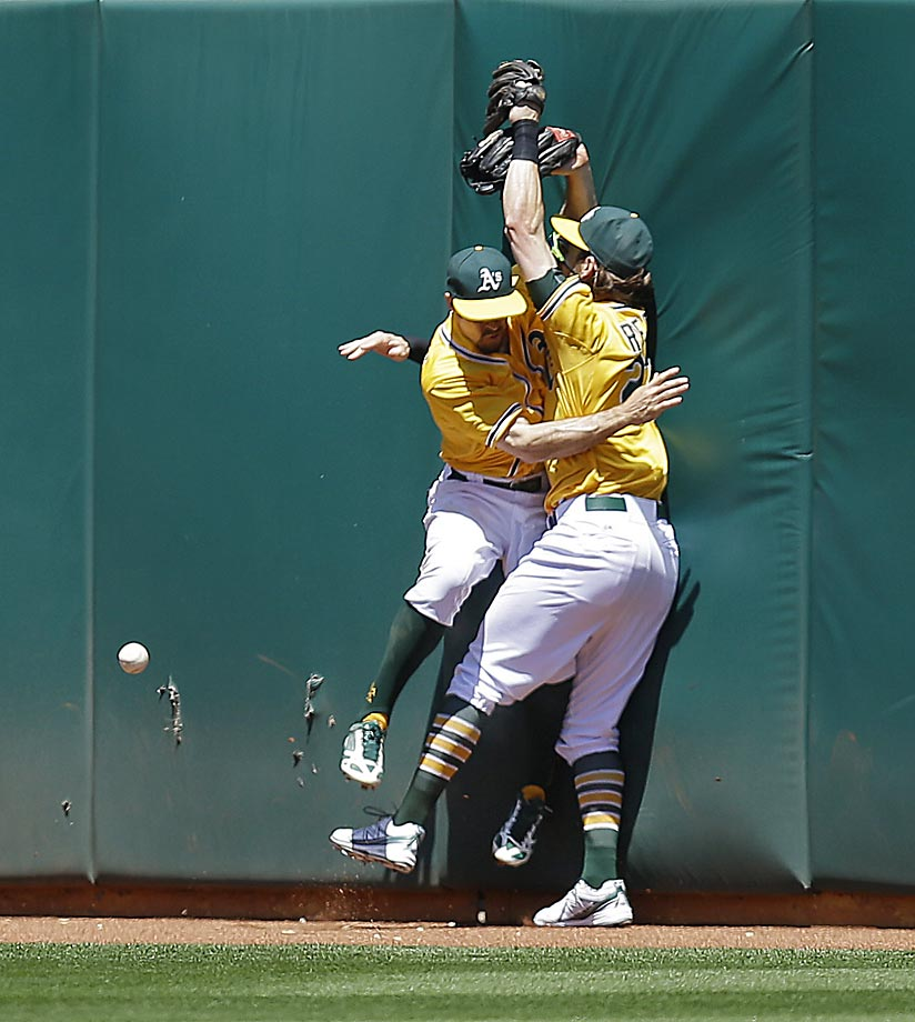 Billy Burns, left, and Josh Reddick of the Oakland A's collide after attempting to catch a triple hit by Justin Upton of the Padres.