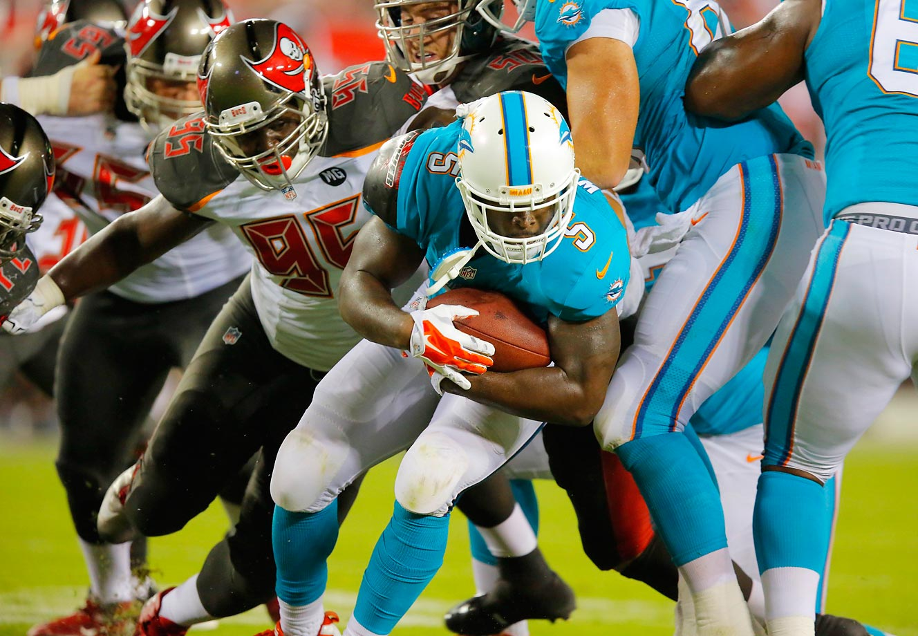 Miami's Damien Williams, an undrafted free-agent running back, maneuvers past Euclid Cummings of the Bucs during both team's second preseason game.