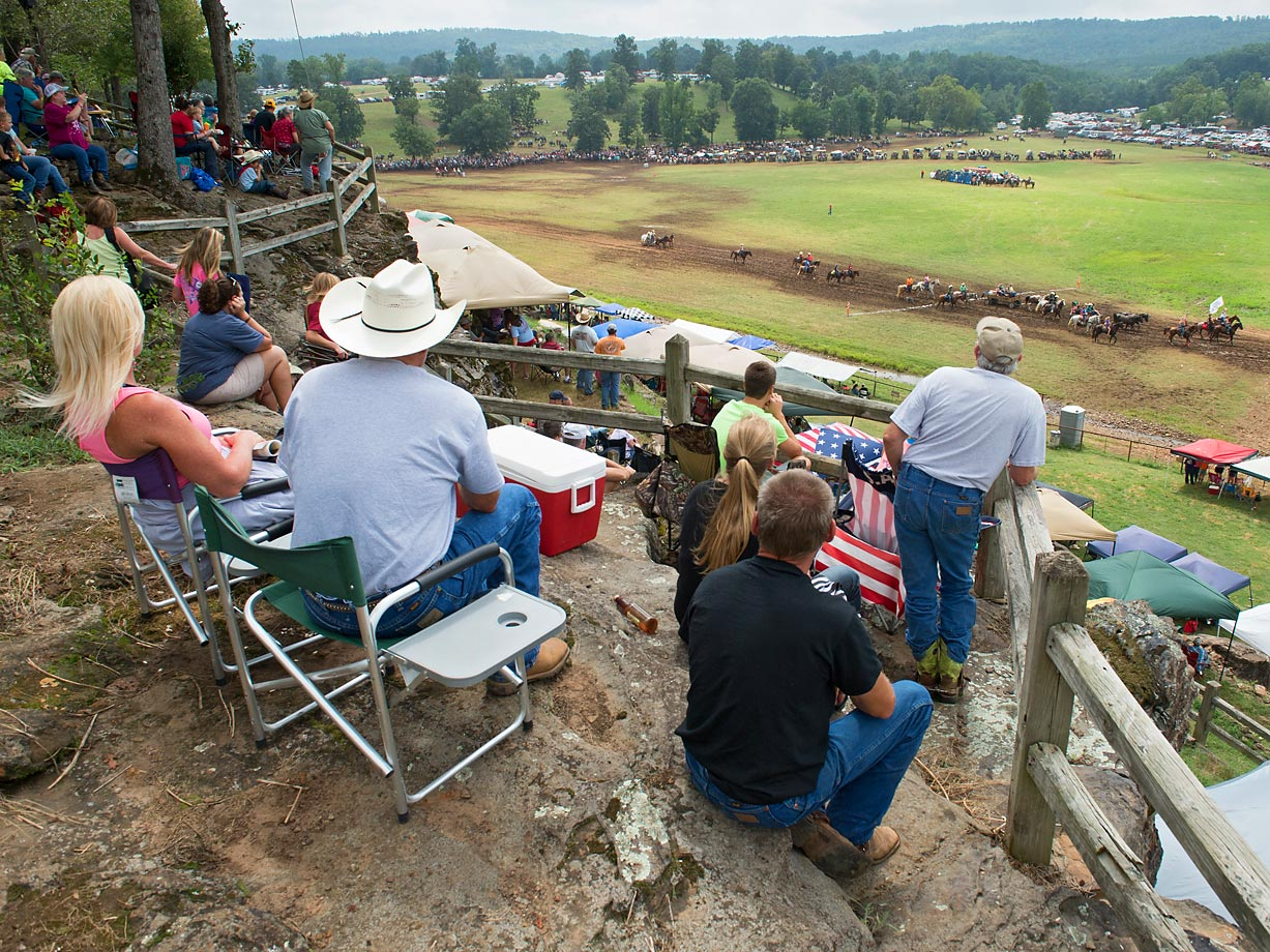 Fans from the cliff watch as the parade of Wagons pass below before the races.