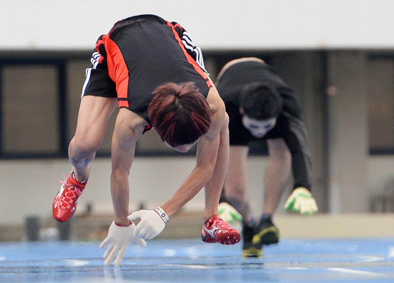 "Kenichi Ito (left) runs with his arms and legs on the track during the quadrupedal 100-meter dash in Tokyo on Nov. 14, 2013. Ito clocked 16.87 seconds to break his own world record and was certified by the Guinness World Records as ""Fastest 100m on All Fours."""