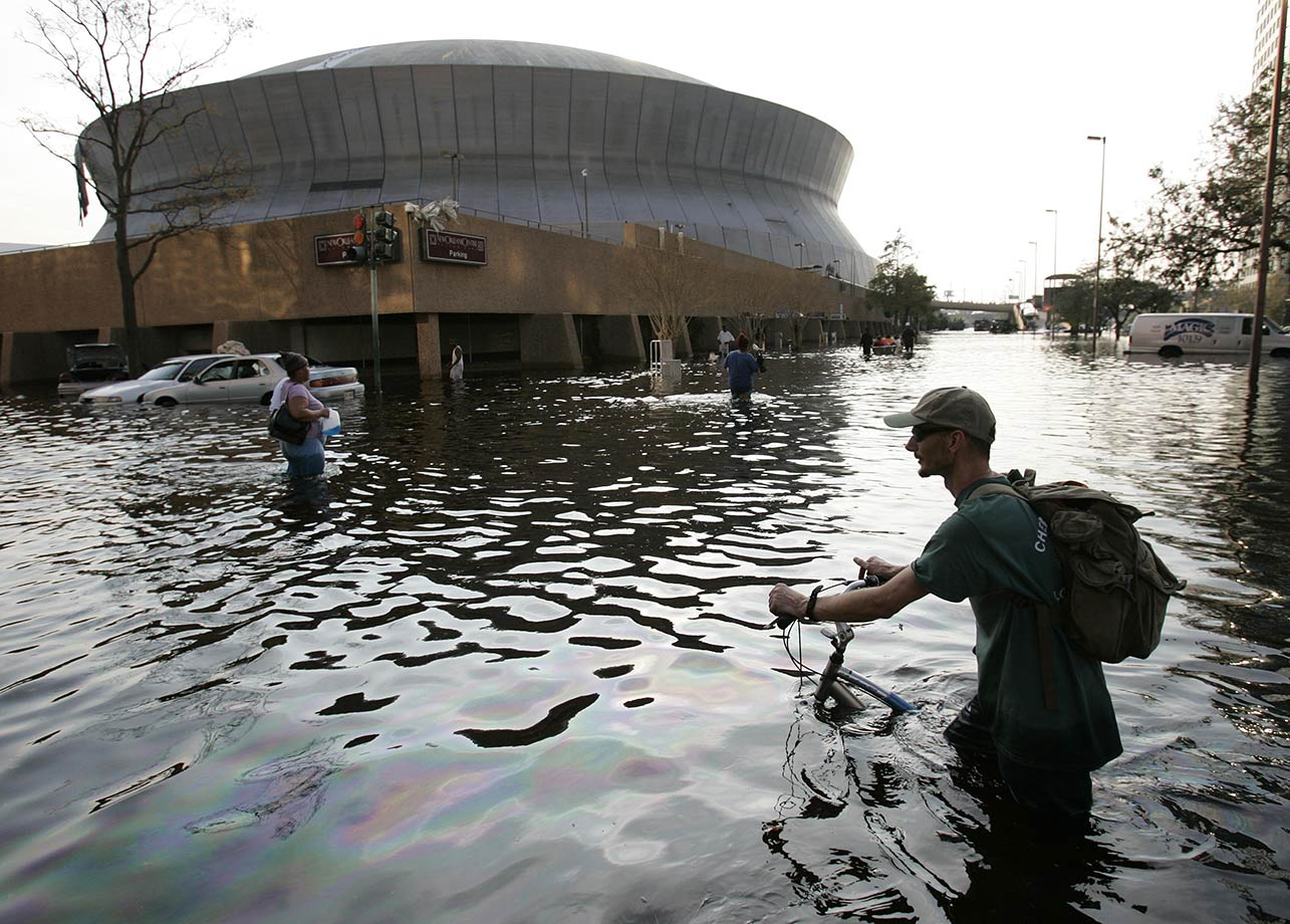 Aug. 31, 2005: A man pushes his bicycle through flood waters near the Superdome. Hurricane Katrina left much of the city under water. Officials called for a mandatory evacuation of the city, but many resident remained in the city and had to be rescued from flooded homes and hotels.