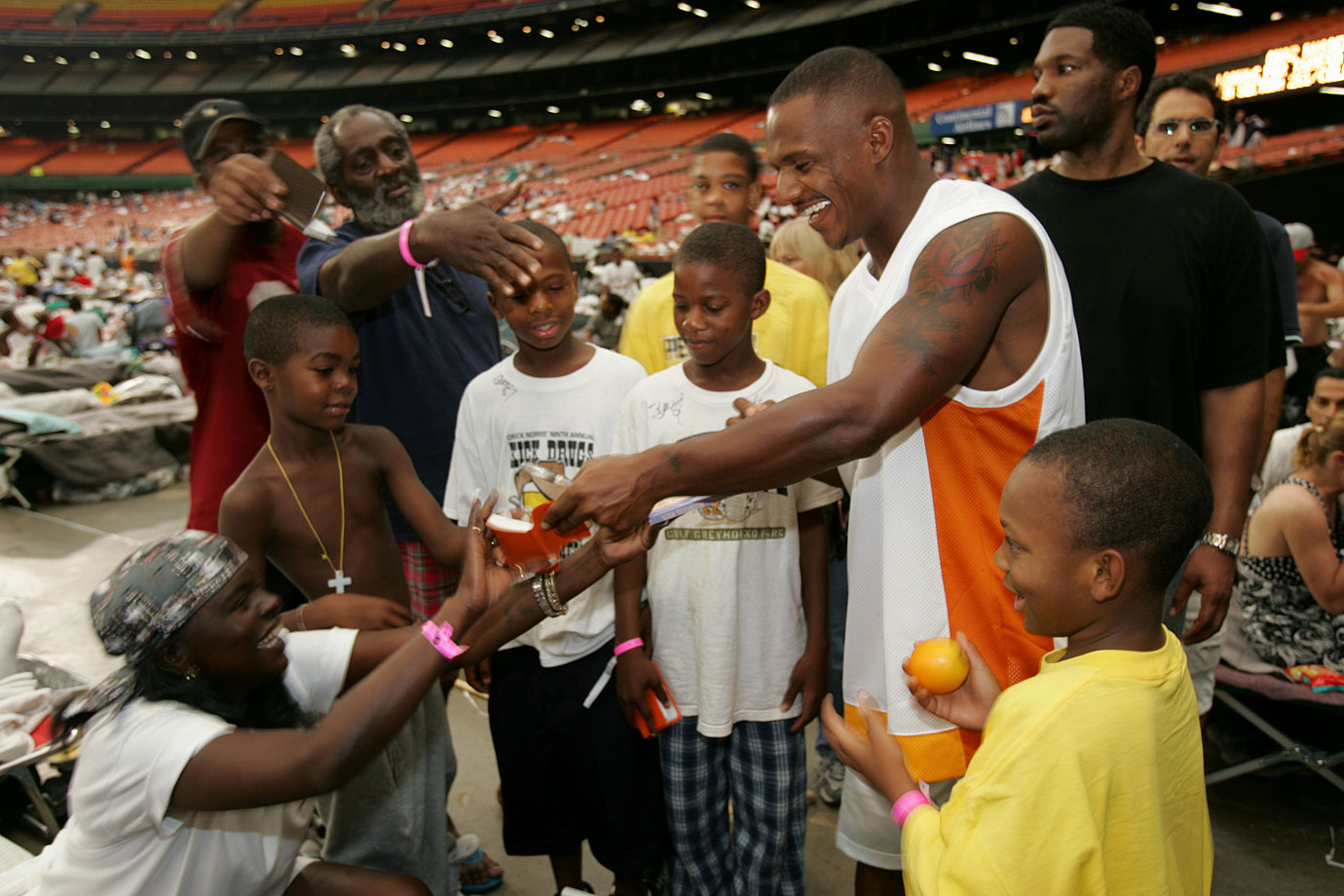 "Sept. 3, 2005: Saints wide receiver Joe Horn visits evacuees sheltered in the Astrodome. ""At the Astrodome it was like a refugee camp,"" said Horn. ""It was just sad. But when the kids ran up to me I got more excited about playing football."""