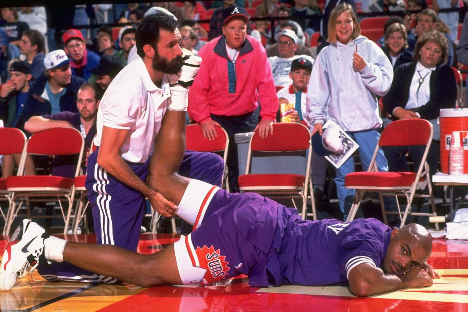 Charles Barkley gets worked on by team trainers on the sidelines during a game against the Milwaukee Bucks.