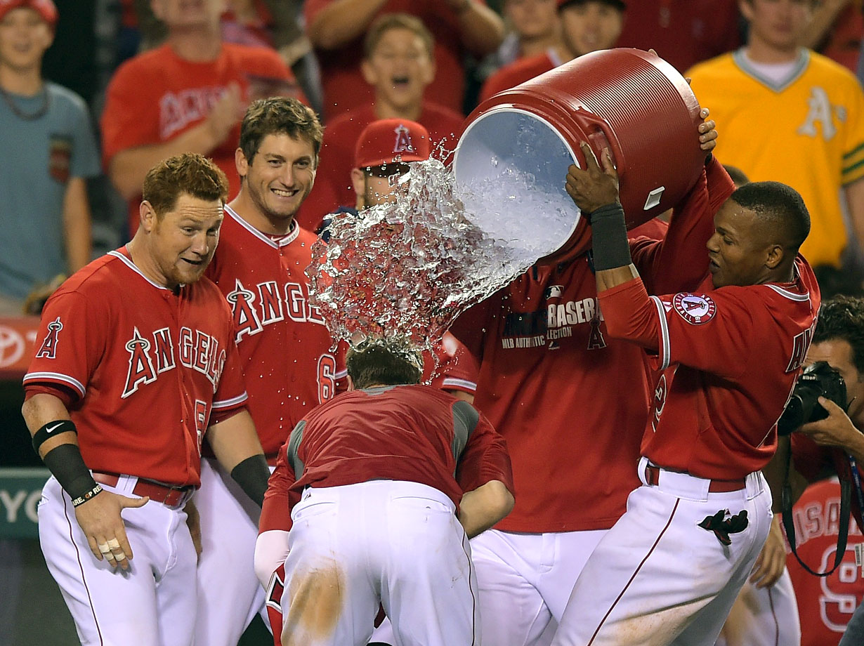 Collin Cowgill is doused by teammate Erick Aybar after hitting a two-out homer in the bottom of the 14th inning of the Angels 2-1 win over the Athletics.