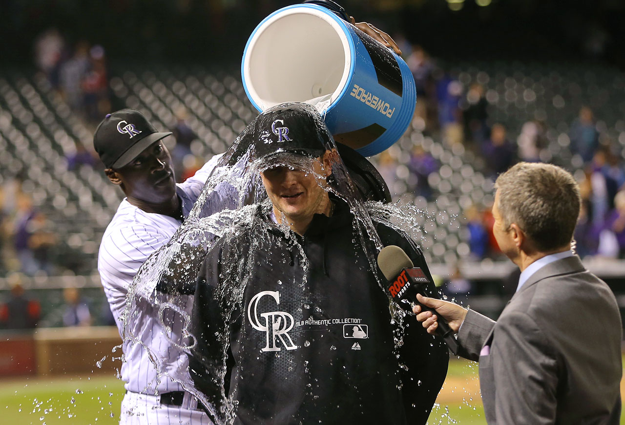 Tyler Matzek is doused by teammate LaTroy Hawkins after earning the win in his major league debut with the Rockies, who defeated the Braves 8-2.