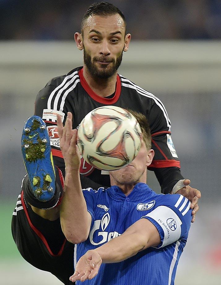 Leverkusen's Omer Toprak and Schalke's Klaas Jan Huntelaar challenge for the ball during their German Bundesliga match.