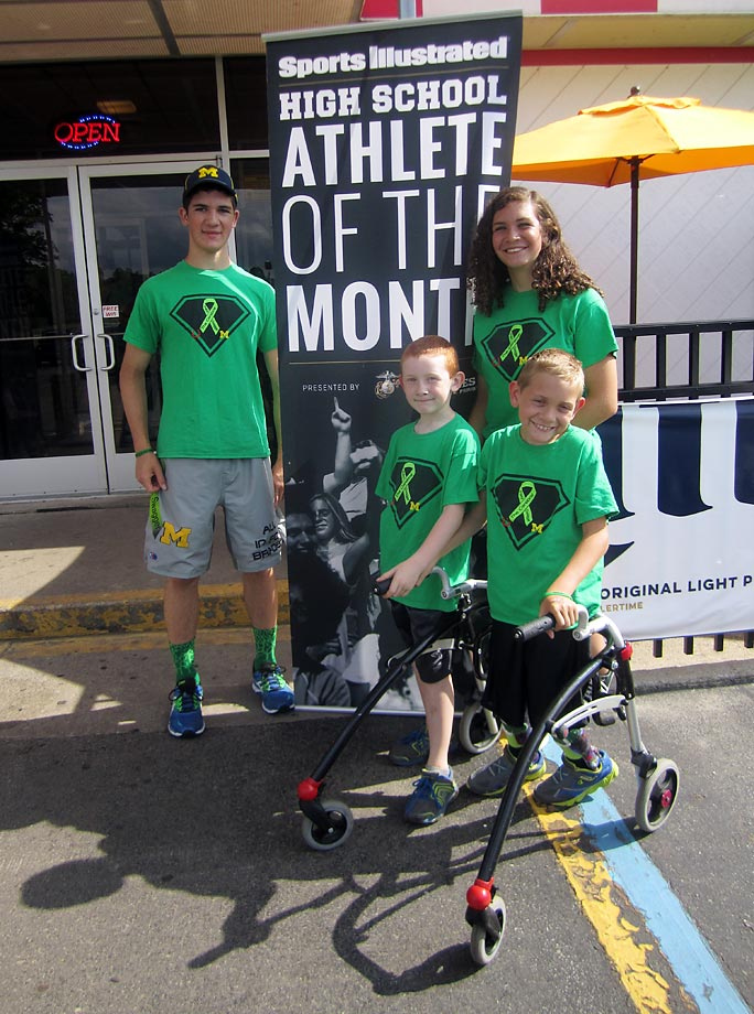 Hunter poses with his younger siblings: sister Kerragan, 14, and brothers Braden, 8 (in walker), and Kellen, 7.