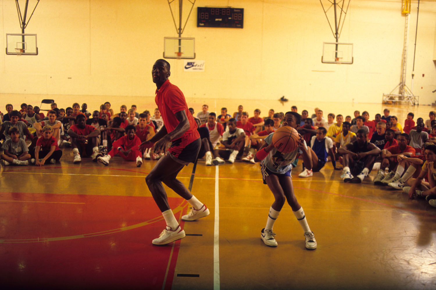 Michael Jordan playing one-on-one against a young basketball player during a basketball camp session at Illinois Benedictine College in 1987.