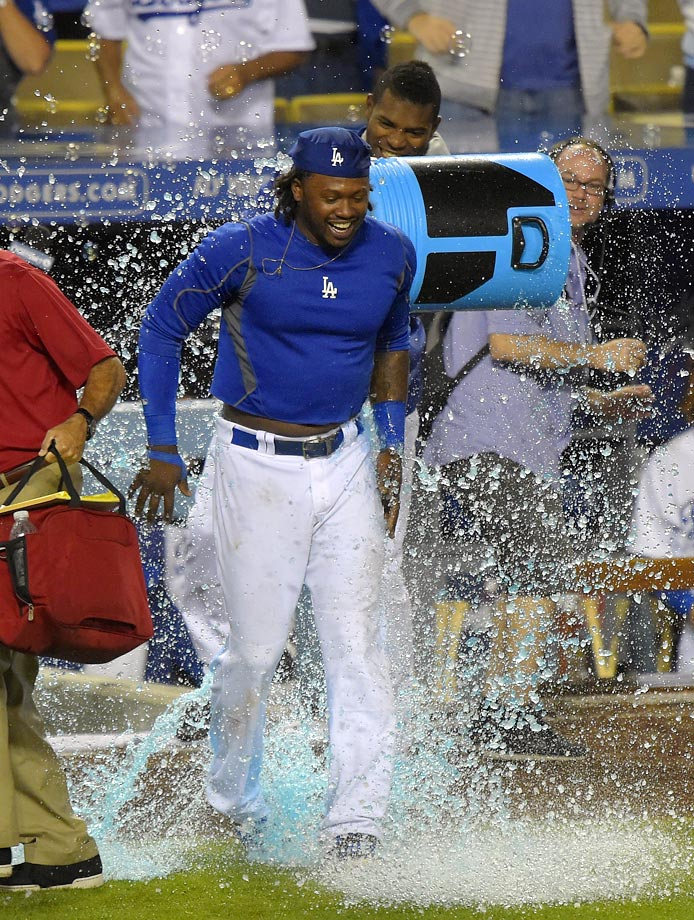 Hanley Ramirez is doused by teammate Yasiel Puig after hitting a three-run home run in the bottom of the 12th inning of the Dodgers 5-2 win over the Cubs.