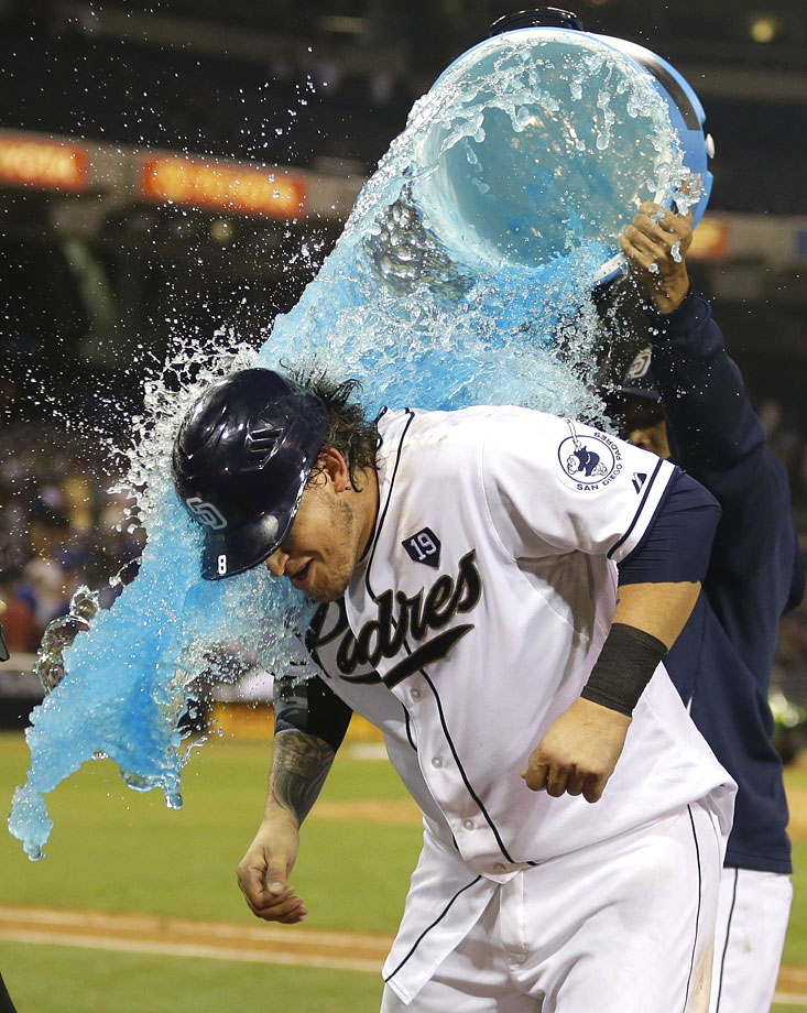 Yasmani Grandal is doused by teammate Everth Cabrera after his walk-off single in the 12th inning of the Padres 3-2 win over the Dodgers.