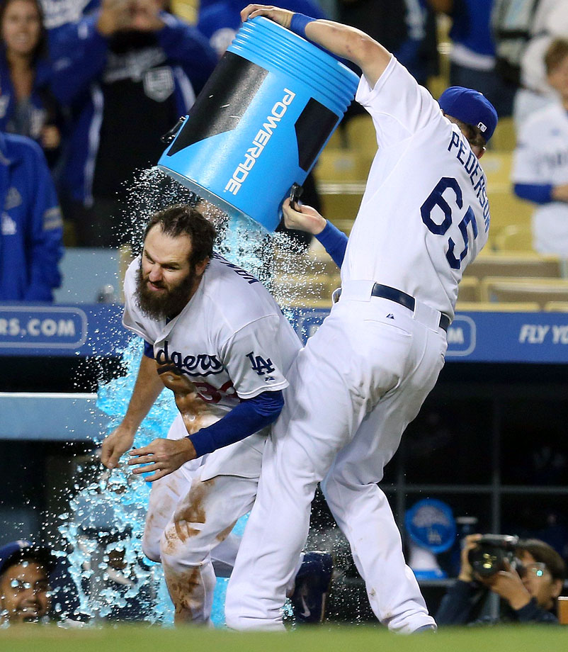 Scott Van Slyke is doused by teammate Joc Pederson after scoring the winning run on Franklin Morales' wild pitch in the 12th inning of the Dodgers 6-5 win over the Rockies.