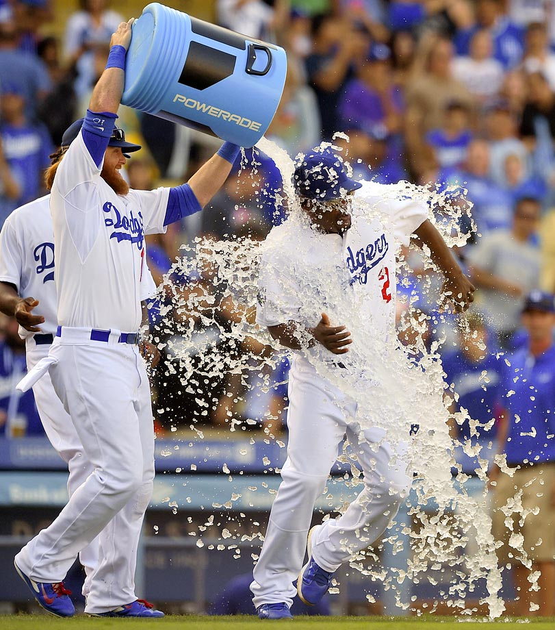 Juan Uribe is doused by teammate Justin Turner after managing the Dodgers to a 10-5 win over the Rockies.