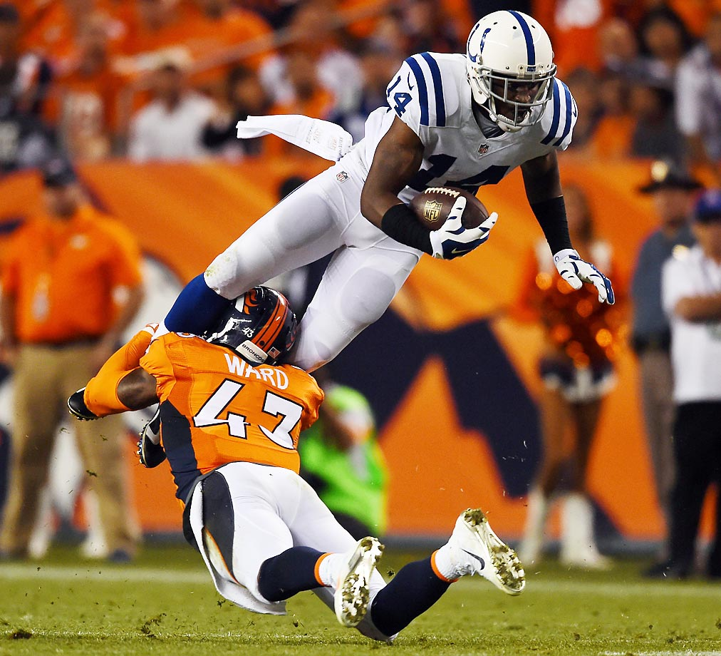 Wide receiver Hakeem Nicks of the Indianapolis Colts is tackled by strong safety T.J. Ward of the Denver Broncos.