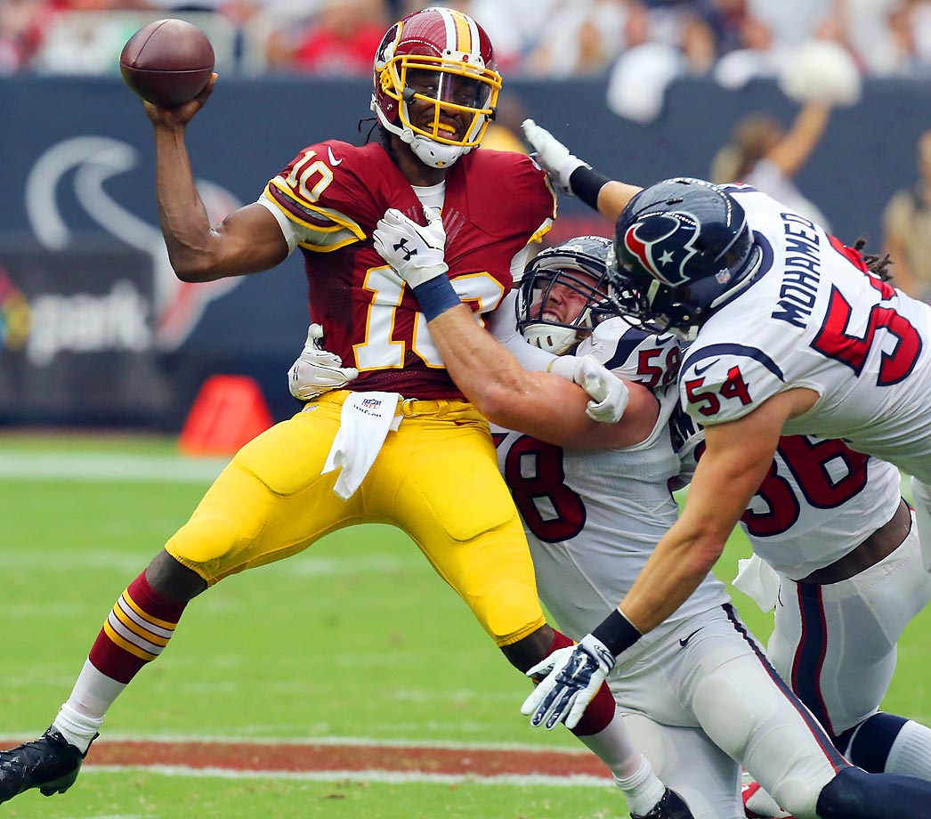 Washington Redskins quarterback Robert Griffin III is sacked by Houston Texans linebackers Brooks Reed and Mike Mohamed.