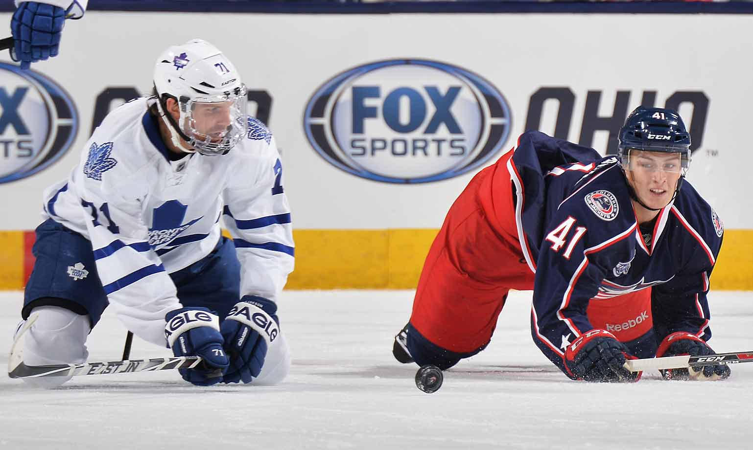 The Maple Leaf and Blue Jacket follow a loose puck during the second period at Nationwide Arena in Columbus on October 31, 2014.